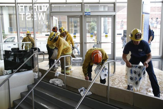 Firefighters work to dam up a stairway inside UCLA's Pauley Pavilion sporting arena as water flows from a broken thirty inch water main that was gushing water onto Sunset Boulevard near the UCLA campus in the Westwood section of Los Angeles July 29, 2014. The geyser from the 100-year old water main flooded parts of the campus and stranded motorists on surrounding streets. REUTERS/Danny Moloshok (UNITED STATES - Tags: DISASTER ENVIRONMENT)