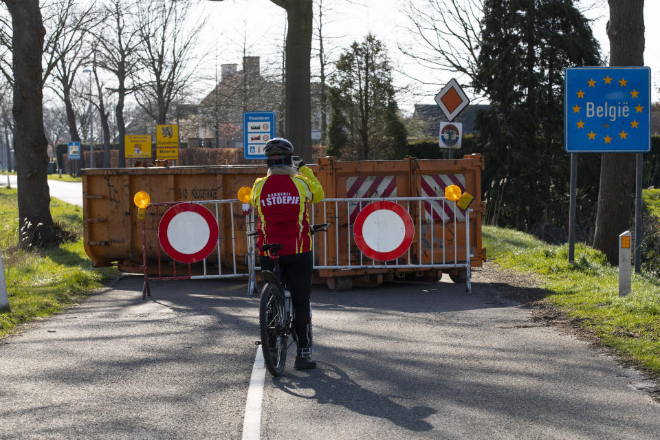 FILE - In this Monday, March 23, 2020 file photo, a cyclist takes images of a barricaded backroad used by locals on the Netherlands border with Belgium between Chaam, southern Netherlands, and Meerle, Northern Belgium. European Union countries are set to adopt a common traffic light system to coordinate traveling across the 27-nation bloc, but a return to a full freedom of movement in the midst of the COVID-19 pandemic remains far from reach. (AP Photo/Peter Dejong, File)