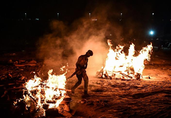 A worker tends to a blazing funeral pyre as another pyre burns nearby