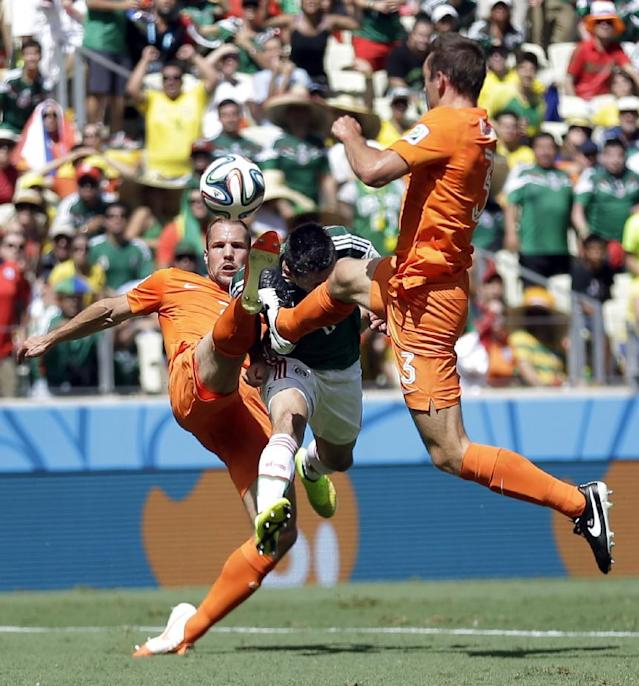 Netherlands' Ron Vlaar, left, and Stefan de Vrij challenge Mexico's Hector Herrera during the World Cup round of 16 soccer match between the Netherlands and Mexico at the Arena Castelao in Fortaleza, Brazil, Sunday, June 29, 2014. (AP Photo/Natacha Pisarenko)