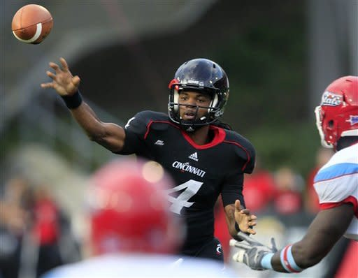 Cincinnati quarterback Munchie Legaux (4) passes against Delaware State during the first half of an NCAA college football game, Saturday, Sept. 15, 2012, in Cincinnati. (AP Photo/Al Behrman)