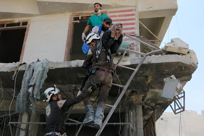 Volunteers evacuate people from a damaged building after a reported airstrike on April 23, 2016 in the rebel-held neighbourhood of Tareeq al-Bab in Aleppo (AFP Photo/Ameer Alhalbi)