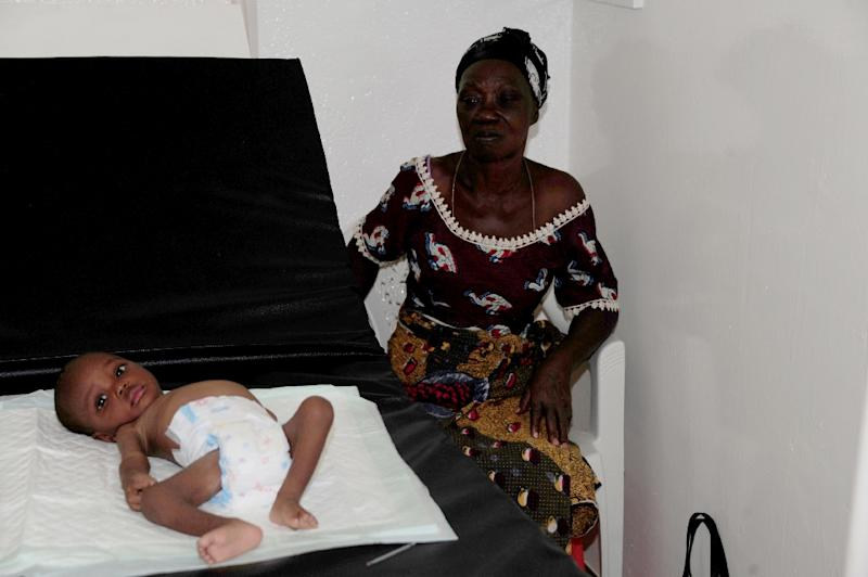 A woman sits next to her baby on April 7, 2015 in Liberia's first ever children's hospital, just opened in Monrovia by Medecins sans Frontieres (MSF), part of the country's response to the daunting challenge of repairing its wrecked health service (AFP Photo/Zoom Dosso)