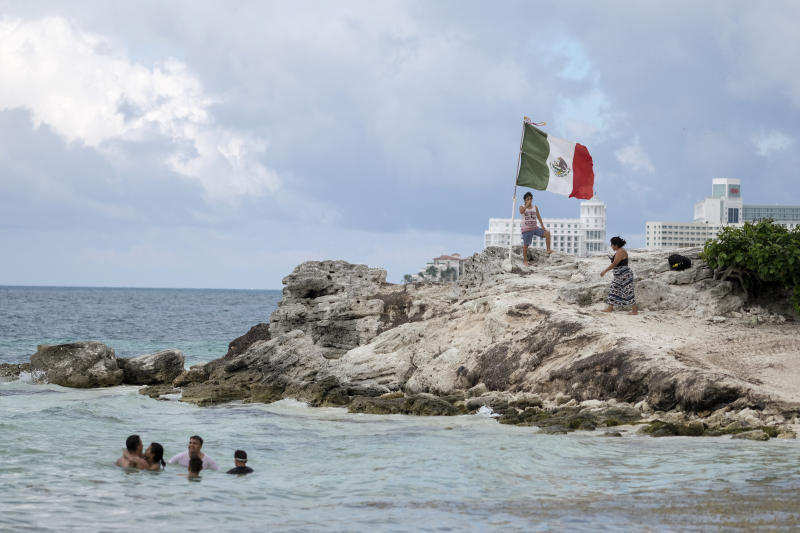 People spend time on the coast of Cancun, Mexico, Saturday, June 13, 2020. An irony of the coronavirus pandemic is that the idyllic beach vacation in Mexico in the brochures really does exist now: the white sand beaches are sparkling clean and empty on the Caribbean coast. (AP Photo/Victor Ruiz)