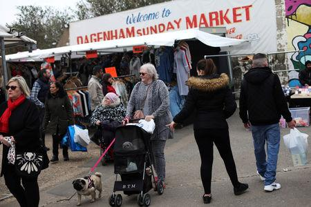 A woman with dogs walks through Dagenham Sunday Market in Dagenham, east London, Britain, March 31 2019. REUTERS/Hannah McKay