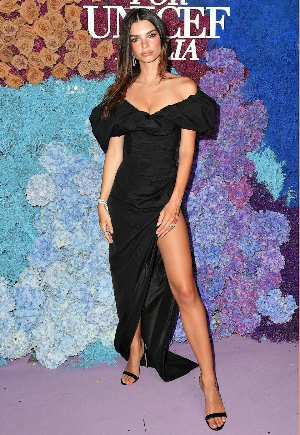 <p>wears an off-the-shoulder ruched gown with puff-sleeve and thigh-high slit.</p>