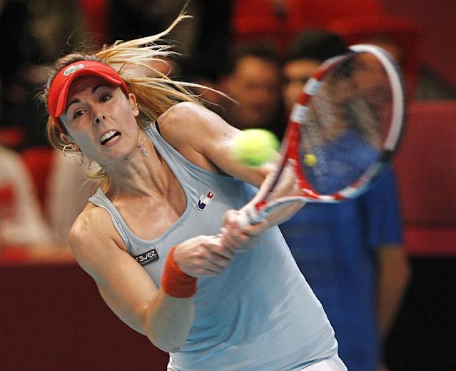 France's Alize Cornet returns the ball to Switzerland's Timea Bacsinszky, during their single match, in the Fed Cup tournament between France and Switzerland, at the Coubertin stadium in Paris, Sunday Feb. 9, 2014. (AP Photo/Remy de la Mauviniere)