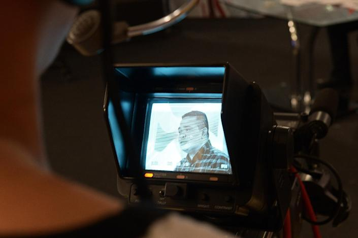 Red Shirts leader Jatuporn Prompan on a cameraman's screen during his live show on Peace TV, reinstated after the ruling junta lifted a ban, October 10, 2014 (AFP Photo/Christophe Archambault)