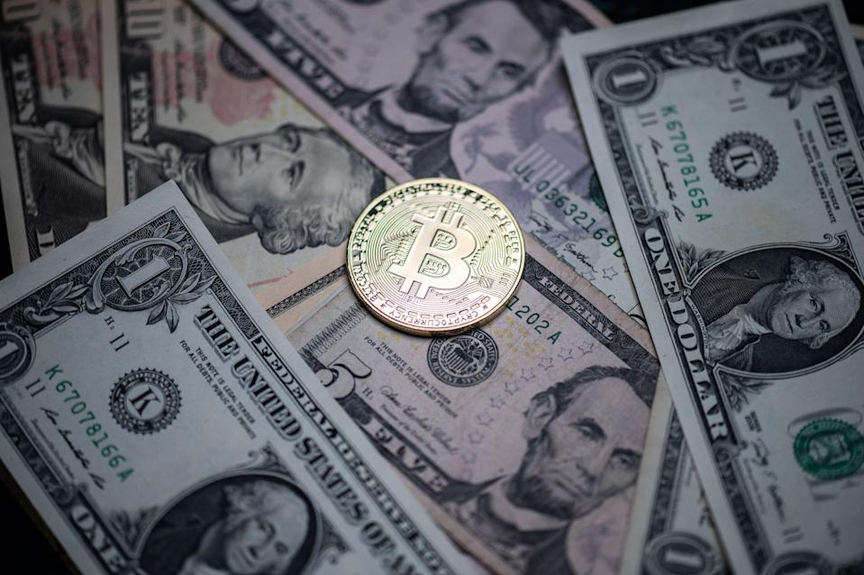 Photograph taken in Paris shows a physical imitation of the Bitcoin crypto currency displayed on US dollars bank notes (AFP via Getty Images)