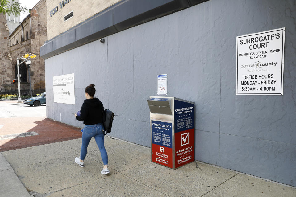 FILE - In this July 1, 2020, file photo, a woman walks past a vote-by-mail drop box for the upcoming New Jersey primary election outside the Camden, N.J., Administration Building. With the Trump administration openly trying to undermine mail-in voting this fall, some election officials around the country are hoping to bypass the Postal Service by installing lots of ballot drop boxes in libraries, community centers and other public places. (AP Photo/Matt Slocum, File)