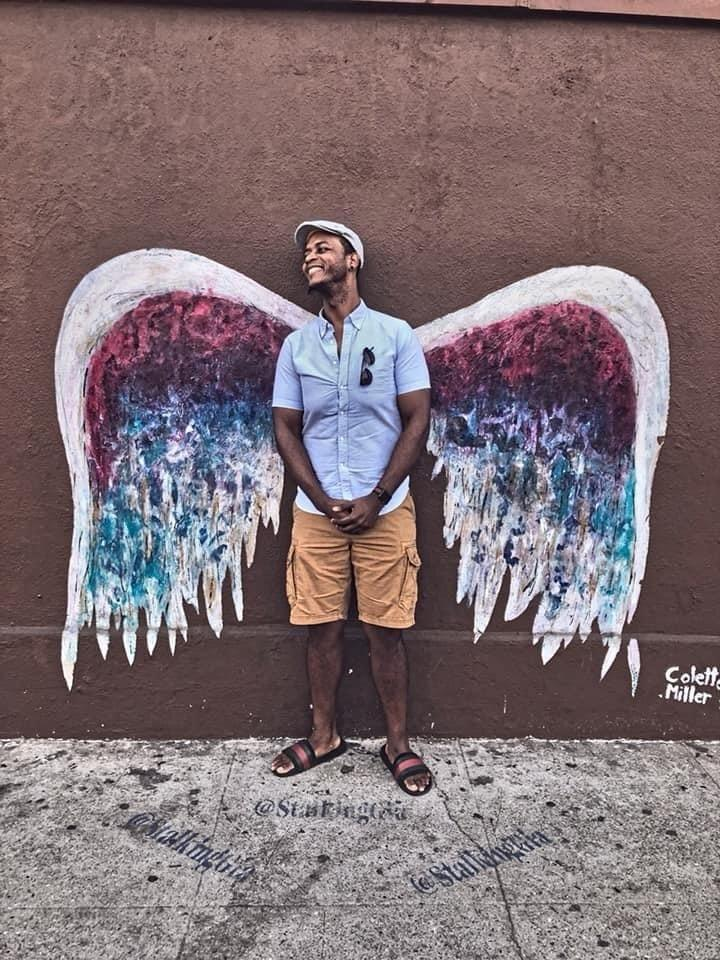 C.T. Taylor, who moved from New York to Los Angeles in 2017, stands in front of a signature piece of L.A. art, a Colette Miller Angel Wings painting.