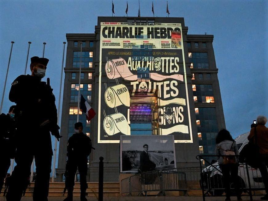 Police officers stand guard as cartoons of French satirical weekly newspaper Charlie Hebdo are projected onto the facade of the Hotel de Region in Montpellier, on 21 October, 2020 (AFP via Getty Images)
