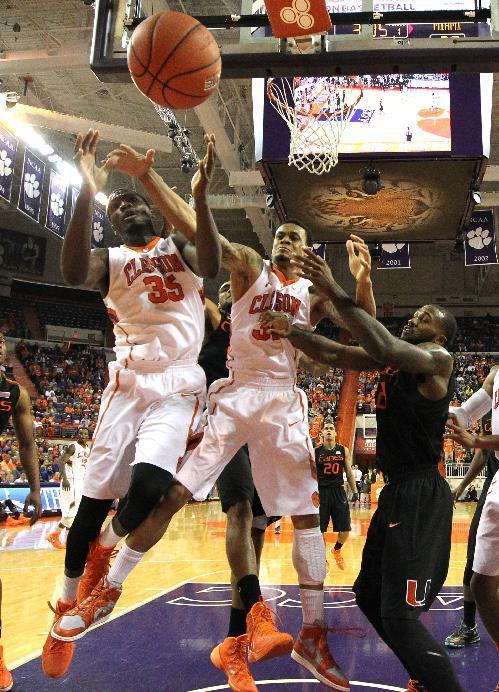 Clemson's Landry Nnoko, left, K.J. McDaniels and Miami's Erik Swoope, right watch a loose ball go out of bounds during the first half of an NCAA college basketball game at Littlejohn Coliseum Tuesday, March 4, 2014, in Clemson, S.C.. (AP PHOTO/Ken Ruinard/ Anderson Independent Mail)
