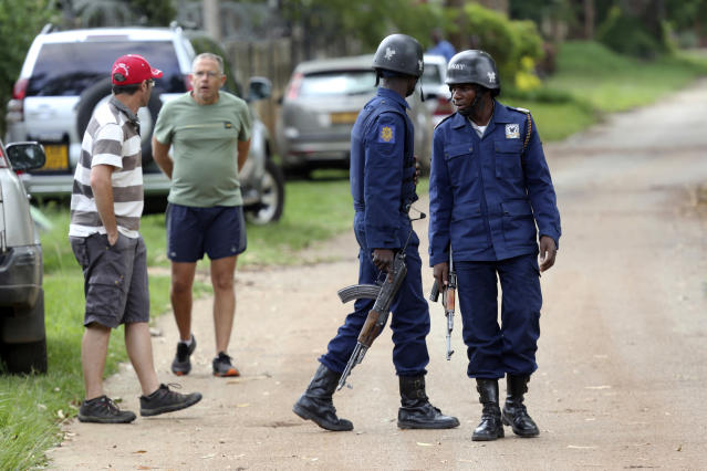 Neighbours watch as armed police surround the residence of Evan Mawarire, an activist and pastor who helped mobilize people to protest against the hike in fuel prices, following his arrest in Harare, Zimbabwe, Wednesday, Jan. 16, 2019. Mawarire was arrested Wednesday for allegedly inciting violence in the protests against the government's increase in fuel prices. (AP Photo/Tsvangirayi Mukwazhi)