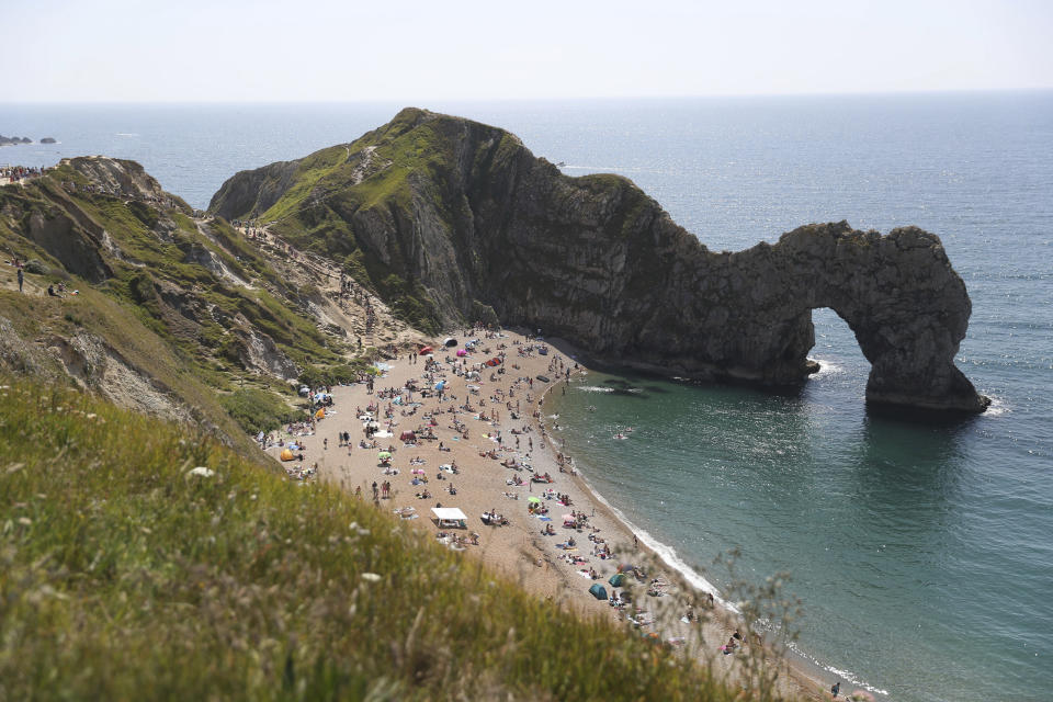 People relax on the beach of Durdle Door beach, as the public are being reminded to practice social distancing following the relaxation of coronavirus lockdown restrictions, near Lulworth in Dorset, England, Saturday May 30, 2020.  (Andrew Matthews/PA via AP)