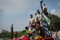 Farmers shout slogans as they climb atop a tractor during the protest in Muzaffarnagar (AFP/Money SHARMA)