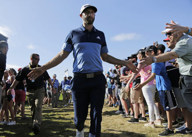 Dustin Johnson greets spectators as he walks to the 12th tee during the third round of the PGA Championship golf tournament, Saturday, May 18, 2019, at Bethpage Black in Farmingdale, N.Y. (AP Photo/Seth Wenig)