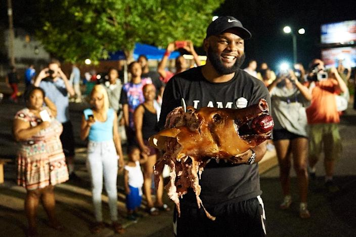 A demonstrator holds the head of roasted pig during a protest march on August 8, 2015 in Ferguson, Missouri (AFP Photo/Michael B. Thomas)