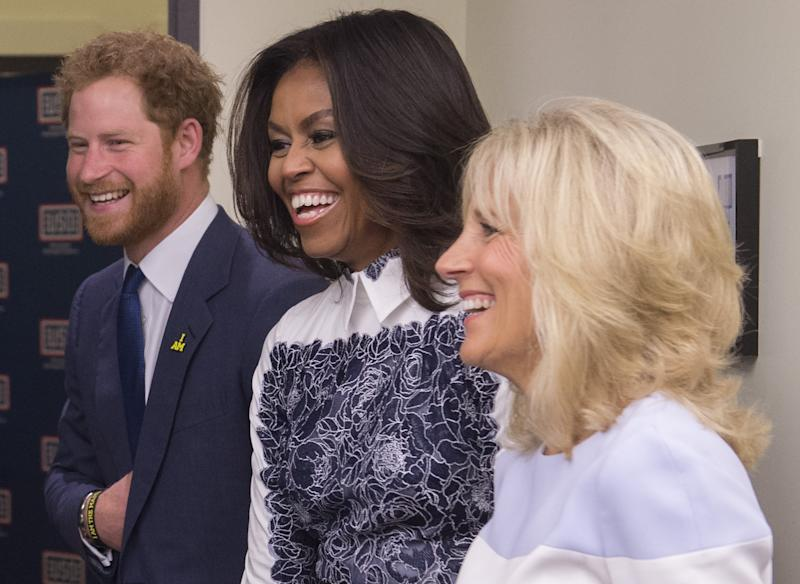 Holding his stomach Wwith Michelle Obama and Jill Biden at the Invictus Games in 2015. (SAUL LOEB via Getty Images)