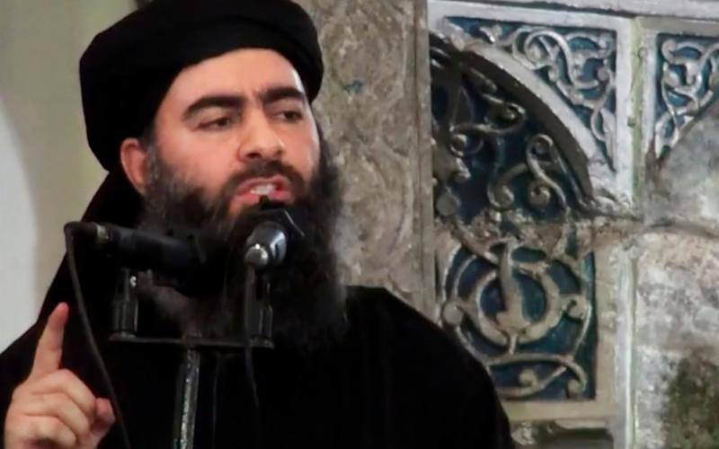Abu Bakr al-Baghdadi, delivering a sermon at a mosque in Iraq during his first public appearance as Isil leader - Militant video