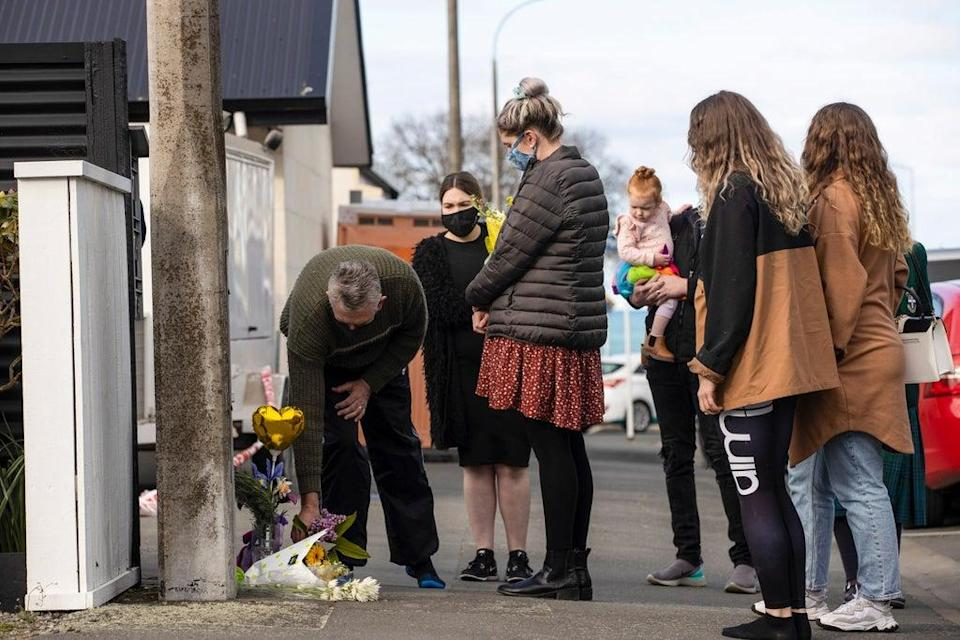 People lay flowers outside of a house where three children were found dead  (AP)