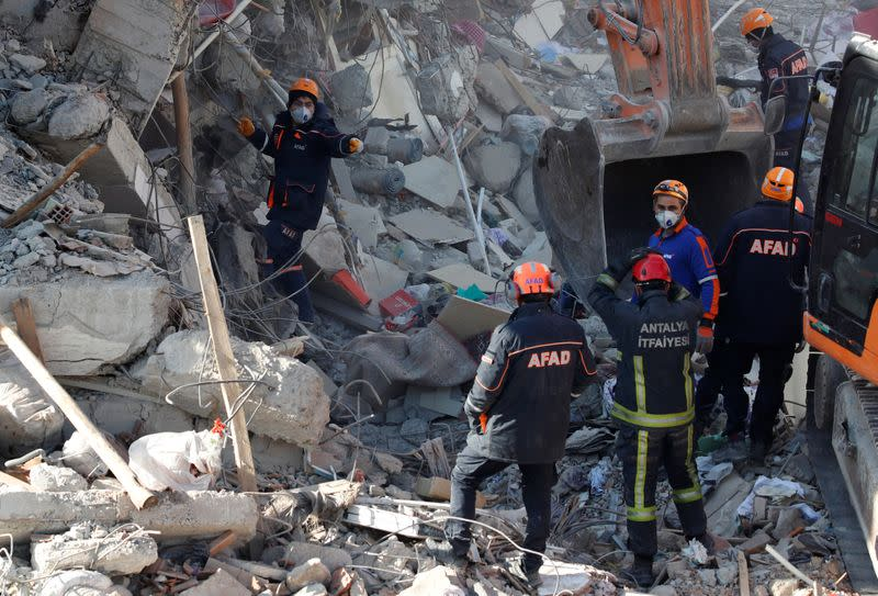 Emergency personnel work at the site of a collapsed building, after an earthquake in Elazig