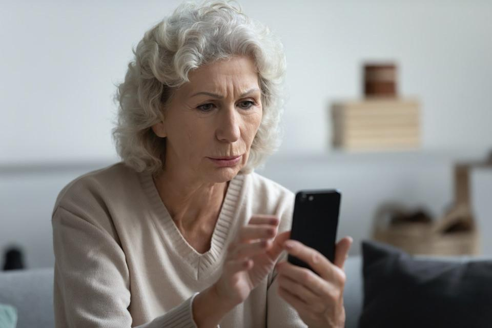 Senior whit woman looking at phone confused
