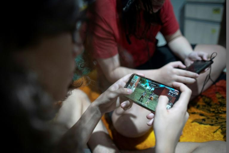 Brothers Guilherme (L), 14, and Arthur, 11, play the mobile game Free Fire at their house in Rio de Janeiro, Brazil