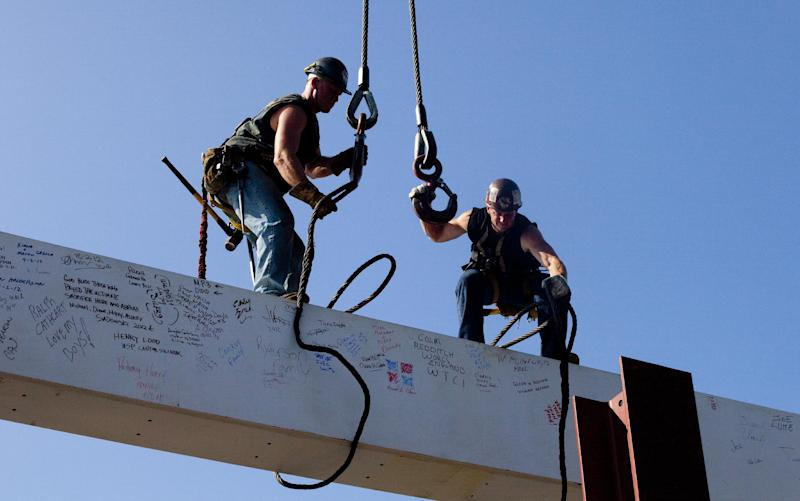 """Ironworkers James Brady, left, and Billy Geoghan release the cables from a steel beam after connecting it on the 104th floor of 1 World Trade Center, Thursday, Aug. 2, 2012 in New York. The beam was signed by President Barack Obama with the notes: """"We remember,"""" ''We rebuild"""" and """"We come back stronger!"""" during a ceremony at the construction site June 14. Since then the beam has been adorned with the autographs of workers and police officers at the site. The beam will be sealed into the structure of the tower, which is scheduled for completion in 2014. (AP Photo/Mark Lennihan)"""