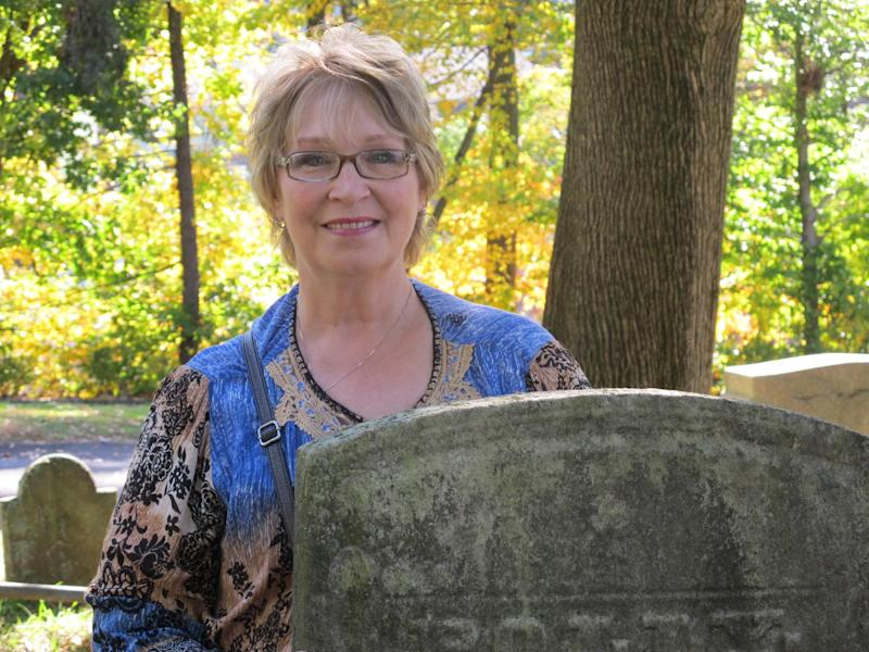 """In this Oct. 18, 2013 photo, Susan Laclair of Granby, Conn., is pictured at historic Sleepy Hollow Cemetery in Sleepy Hollow, N.Y. The village of Sleepy Hollow is even busier than usual this Halloween, thanks to a new """"Sleepy Hollow"""" TV series inspired by the tale of the Headless Horseman. """"We were watching the show, and I was remembering the old story I'd read as a kid. I love anything to do with history, and I said, 'There's a real Sleepy Hollow. Let's go for a few days, """" said Laclair. (AP Photo/Jim Fitzgerald)"""