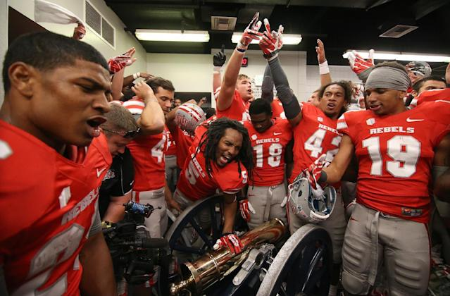 UNLV celebrates around the Fremont Cannon in the locker room following an NCAA football game against Nevada in Reno, Nev., on Saturday, Oct. 26, 2013. UNLV defeated Nevada 27-22. (AP Photo/Cathleen Allison)