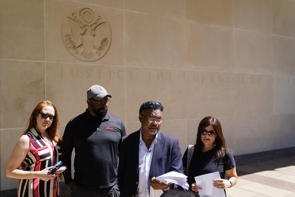 """From the left, Brooke Vaughn, her husband former NFL player Clarence Vaughn III, former NFL player Ken Jenkins and his wife Amy Lewis read a letter before delivering tens of thousands of petitions demanding equal treatment for everyone involved in the settlement of concussion claims against the NFL, to the federal courthouse in Philadelphia, Friday, May 14, 2021. Thousands of retired Black professional football players, their families and supporters are demanding an end to the controversial use of """"race-norming"""" to determine which players are eligible for payouts in the NFL's $1 billion settlement of brain injury claims, a system experts say is discriminatory. (AP Photo/Matt Rourke)"""