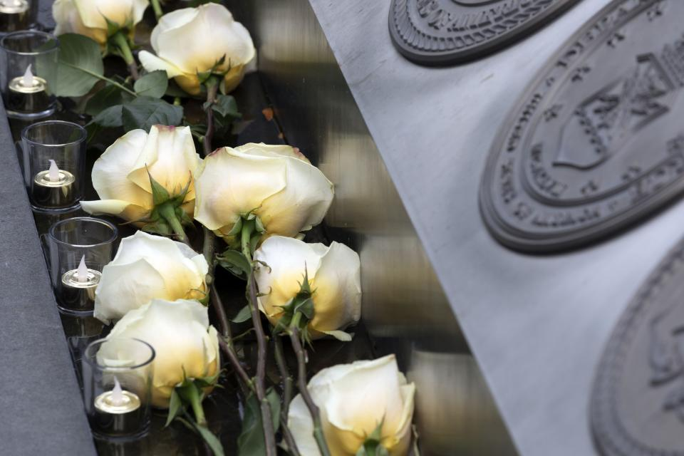 Roses and candles lie at the Massachusetts Fallen Heroes Memorial, Saturday after being placed during a ceremony, Aug. 28, 2021, in Boston. The ceremony was held to honor the U.S. service members killed in a suicide bombing at the airport in Kabul, Afghanistan, including Marine Sgt. Johanny Rosario Pichardo of Lawrence, Mass. (AP Photo/Michael Dwyer)