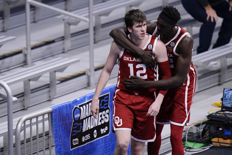Oklahoma guard Austin Reaves (12) reacts to committing a foul and is hugged by teammate Kur Kuath while playing Gonzaga in the second half of a college basketball game in the second round of the NCAA tournament at Hinkle Fieldhouse in Indianapolis, Monday, March 22, 2021. (AP Photo/AJ Mast)