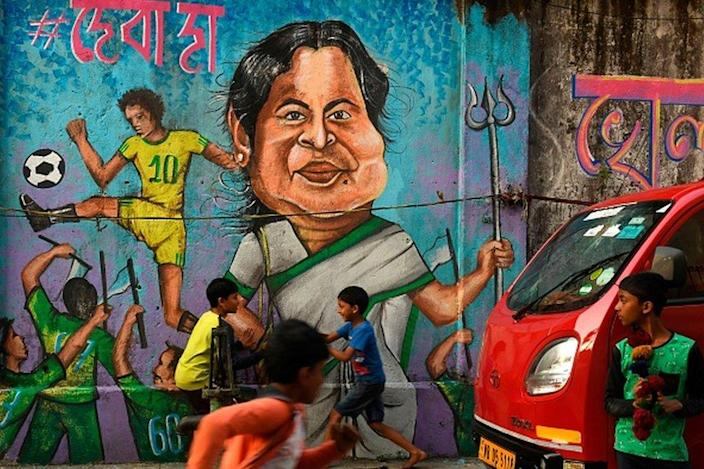 Children are playing in front of a wall graffiti depicting the leader of the Trinamor Conference (TMC) and Prime Minister Mama Tabanerjee of West Bengal prior to the state legislature elections in Kolkata on February 27, 2021. ..