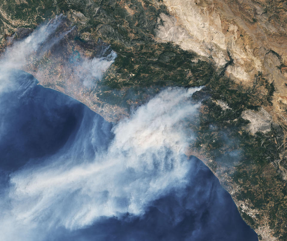In this Saturday, July 31, 2021, Landsat 8 satellite Operational Land Imager (OLI) image taken in natural color and provided by NASA, wildfires burn near the coastal towns of Manavgat, left, and Alanya, right, along the coast in southern Turkey. (NASA via AP