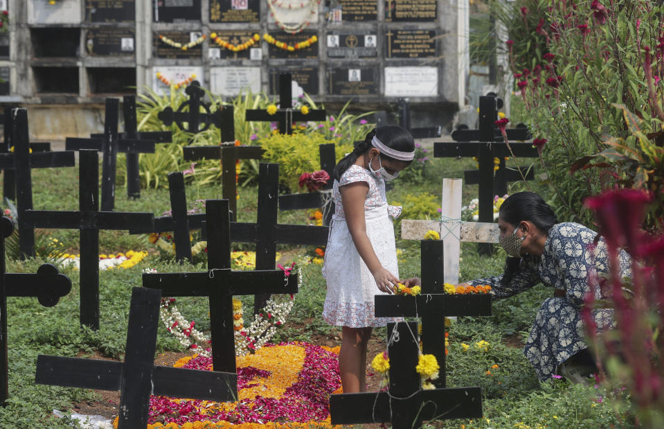 Relatives wearing face masks as a precaution against the coronavirus put flowers at the grave of a deceased relative during All Souls Day in Mumbai, India, Monday, Nov. 2, 2020. (AP Photo/Rafiq Maqbool)