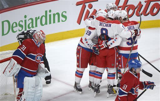 Washington Capitals' Nicklas Backstrom (19) celebrates with teammates Alexander Ovechkin (8) and Mike Green (52) after scoring against Montreal Canadiens goaltender Carey Price, left, during the second period of an NHL hockey game in Montreal, Saturday, April 20, 2013. (AP Photo/The Canadian Press, Graham Hughes)