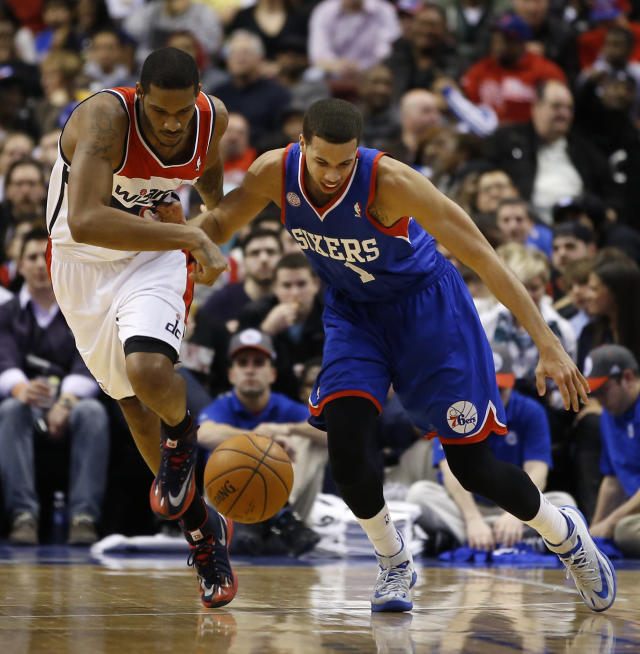 Philadelphia 76ers' Michael Carter-Williams, right, and Washington Wizards' Trevor Ariza battle for a loose ball during the first half of an NBA basketball game, Saturday, March 1, 2014, in Philadelphia. (AP Photo/Matt Slocum)