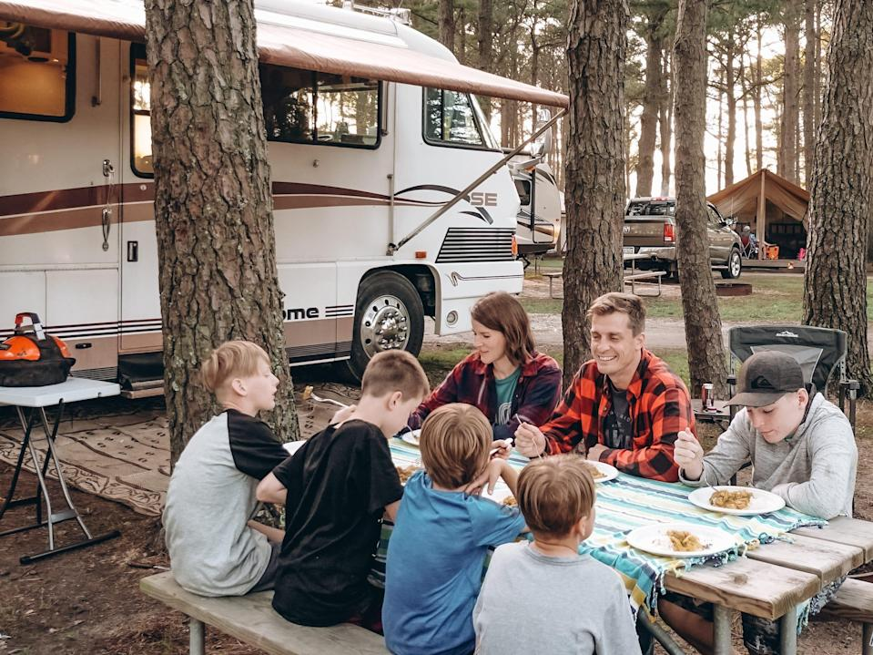 the walker family eating at a table outside in front of their RV