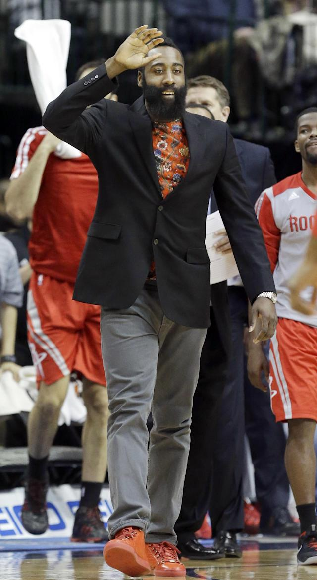 Houston Rockets shooting guard James Harden wears street clothes as he cheers his team on in a timeout during the second half of an NBA basketball game against the Dallas Mavericks, Wednesday, Jan. 29, 2014, in Dallas. Harden did not play in the Rockets 117-115 win. (AP Photo/LM Otero)