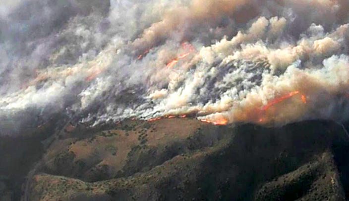 This photo from video provided by KNBC-TV shows smoke and flames from the Silverado fire that is threatening areas near Irvine in Southern California's Orange County Monday, Oct. 26, 2020. Driven by strong, gusting winds, the fire grew rapidly Mondy morning. (KNBC-TV via AP)
