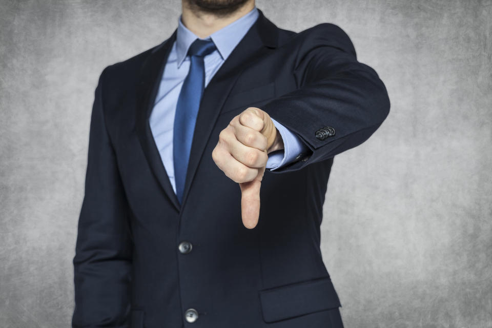 A businessman in a suit giving the thumbs-down sign.