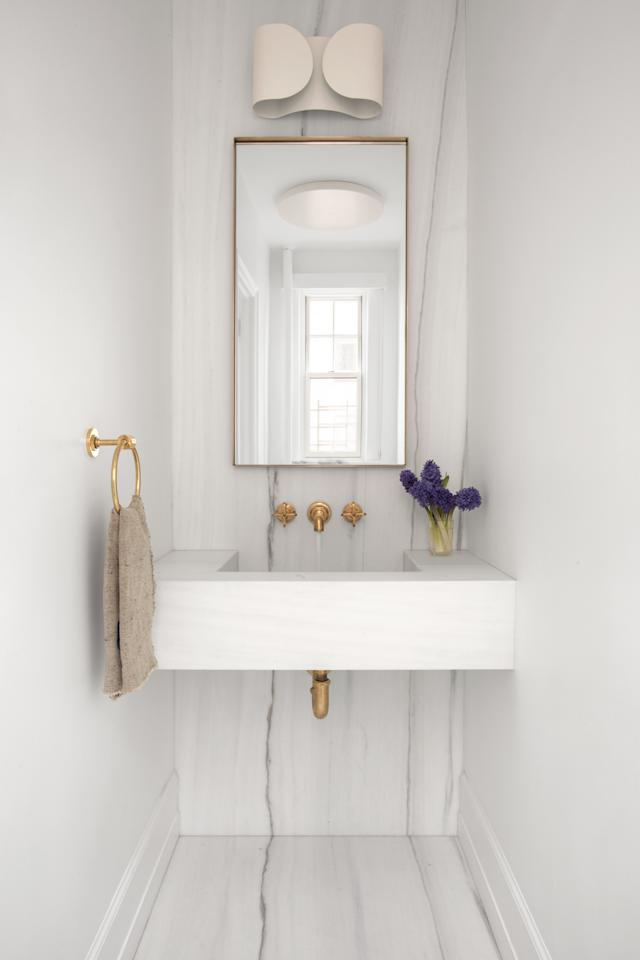 """""""Unlike the kitchen, go for a more minimal display in the bathroom. It's a cleanliness thing,"""" King explains.  A perfect example is this marble-clad bathroom he styled for <em>AD</em>'s March 2019 issue."""