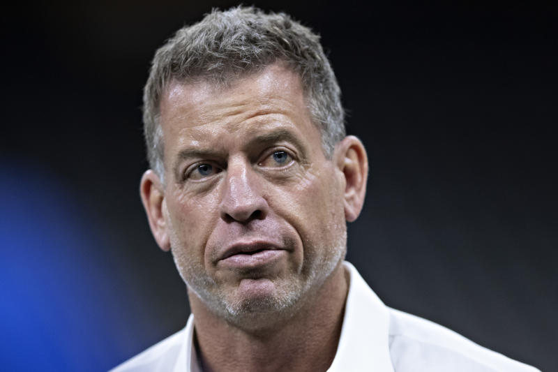 A gold jacket and fistful of rings doesn't make Troy Aikman immune from the bait of a Twitter feud. (Getty)