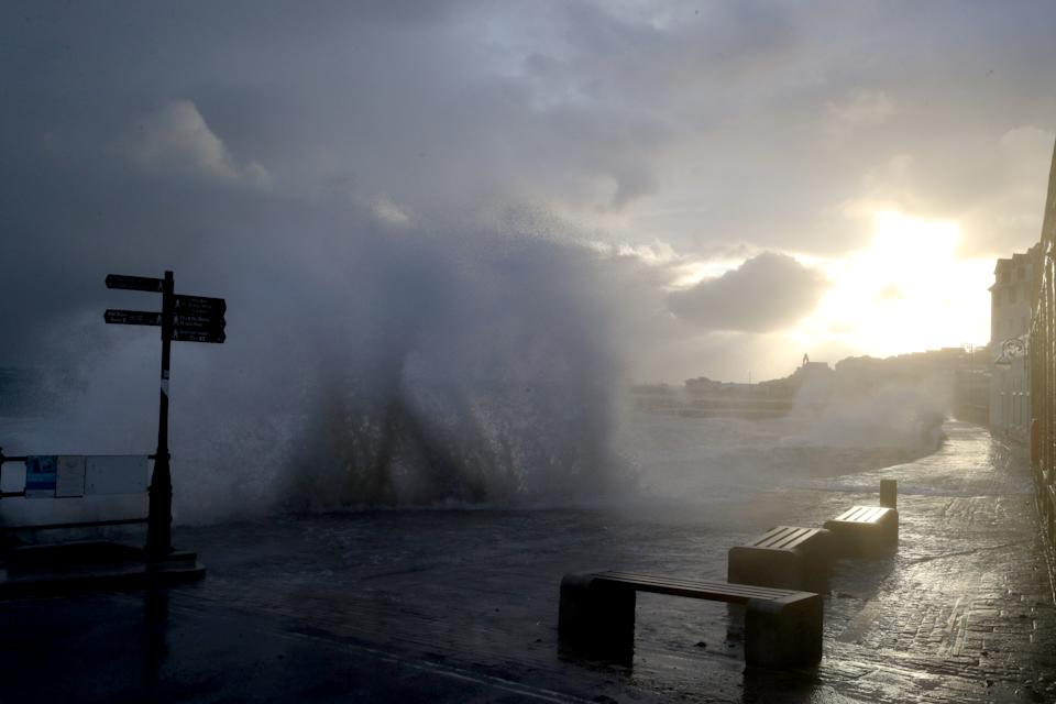 The sun rises behind the clouds as waves crash along the coast at Swanage in Dorset. Parts of the UK are preparing to be lashed by heavy rain and high winds as Storm Alex heralds the arrival of a stretch of bad weather over the weekend.
