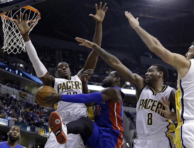 Detroit Pistons guard Will Bynum, left center, makes a pass between Indiana Pacers' Ian Mahinmi, left, Rasual Butler, right center, and Luis Scola in the first half of an NBA basketball game in Indianapolis, Monday, Dec. 16, 2013. (AP Photo/Michael Conroy)