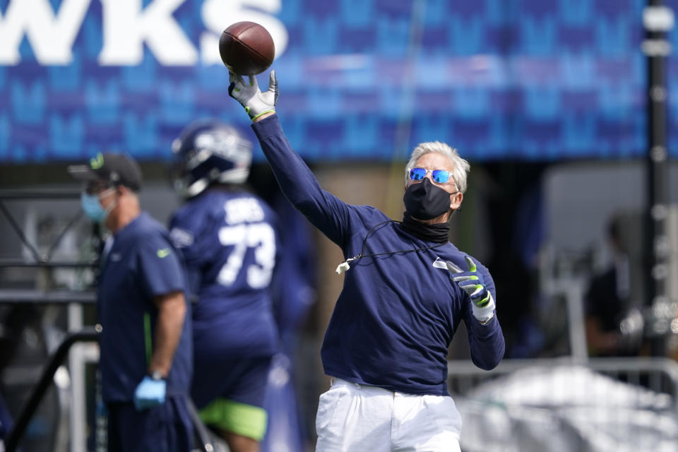 Seattle Seahawks head coach Pete Carroll throws a football during NFL football training camp, Wednesday, Aug. 12, 2020, in Renton, Wash. (AP Photo/Ted S. Warren, Pool)