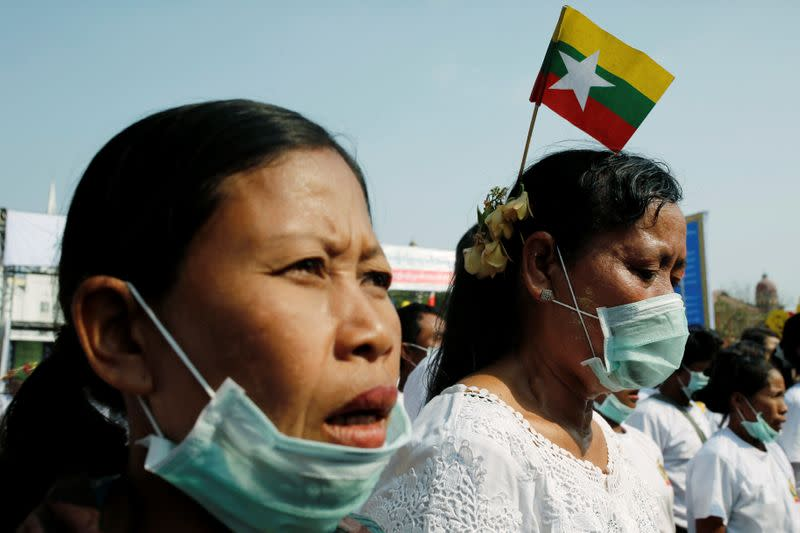 Participants hold Myanmar flags and pray before a nationalist rally in Yangon,