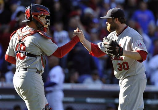 St. Louis Cardinals' Tony Cruz and Jason Motte (30) celebrate their 5-4 victory in 10 innings over the Chicago Cubs in a baseball game Saturday, Sept. 22, 2012, in Chicago. (AP Photo/Jim Prisching)
